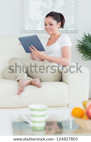 Smiling woman sitting in a living room on the couch and using a tablet pc