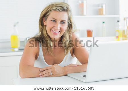 Smiling woman sitting in the kitchen and using laptop