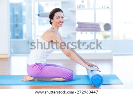 Smiling woman sitting on exercise mat in medical office