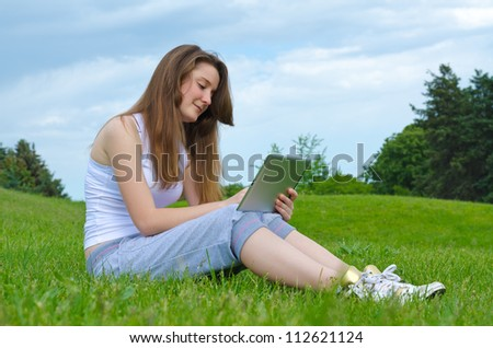 Smiling woman sitting on grass in a lush green park using a touchscreen tablet
