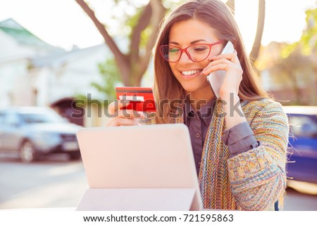 Smiling woman sitting outdoors talking on mobile phone making online payment on her tablet computer outside on a sunny autumn day
