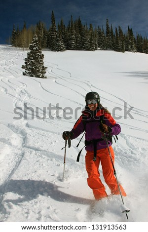 Smiling woman skiing powder snow in the Utah mountains, USA.