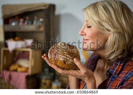Smiling woman smelling a round loaf of bread at counter in bake shop