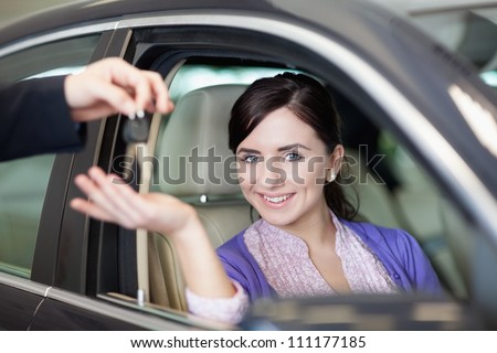 Smiling woman smiles as she sits in a car while receiving keys