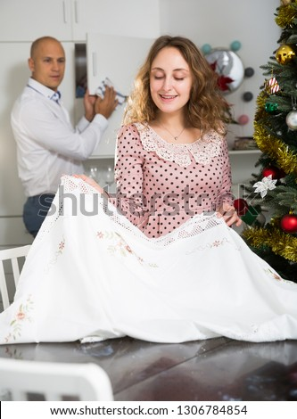 Smiling woman spreading tablecloth on table before New Year dinner while man cleaning furniture