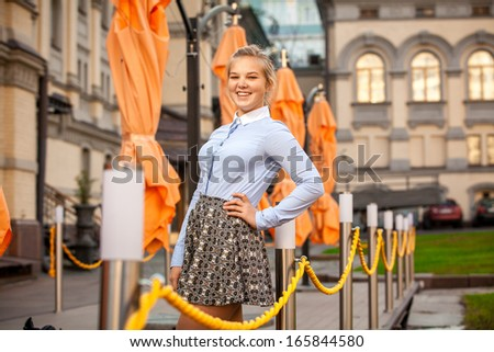 Smiling woman standing on restaurant terrace with umbrellas