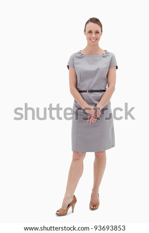 Smiling woman standing up and holding her hands against white background
