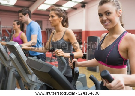 Smiling woman stepping on a step machine in gym