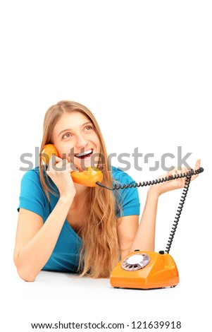 Smiling woman talking on an old styled phone isolated on white background