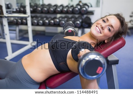 Smiling woman training with weights in gym