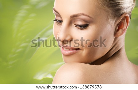 smiling woman turned back and looking down. closeup portrait on green blurred nature background - stock photo