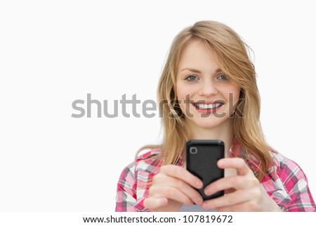 Smiling woman using a mobile phone while looking at camera against a white background