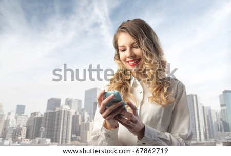 Smiling woman using a mobile phone with cityscape on the background - stock photo