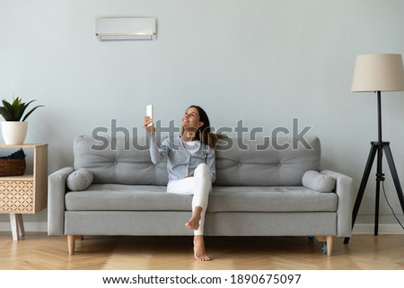Smiling woman using air conditioner remote controller, sitting on cozy couch at home full length, happy young female relaxing setting comfort temperature in modern living room, enjoy fresh air