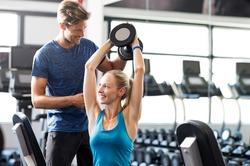 Smiling woman using dumbbells with personal trainer in the fitness room. Young woman doing weight exercises with assistance of man in gym. Personal coach helping girl to do exercises with dumbbells.