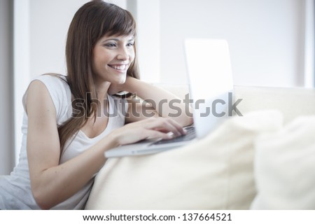 Smiling woman using her laptop sitting on the couch in her home. She is looking at laptop and smiling