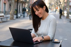 Smiling woman using laptop at cafe terrace. Young beautiful girl working on computerin the street.