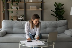 Smiling woman using laptop, managing finances, planning budget, sitting on couch at home, checking financial documents, domestic bills, browsing online banking service, satisfied by money refund