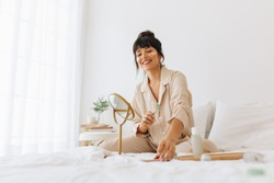 Smiling woman using roller to massage face sitting on bed at home. Woman sitting in bedroom applying cosmetics and skin care products.
