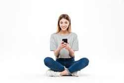 Smiling woman using smartphone and looking camera while sitting on floor cross-legged isolated over white