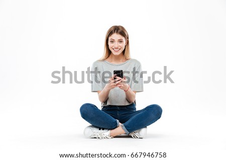 Smiling woman using smartphone and looking camera while sitting on floor cross-legged isolated over white #667946758