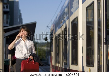 Smiling woman walks while talking on cell phone and holding red handbag. She is walking next to a train. Horizontally framed photo.