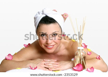 Smiling woman wearing head turban relaxes amongst fragrant rose petals and aroma sticks.