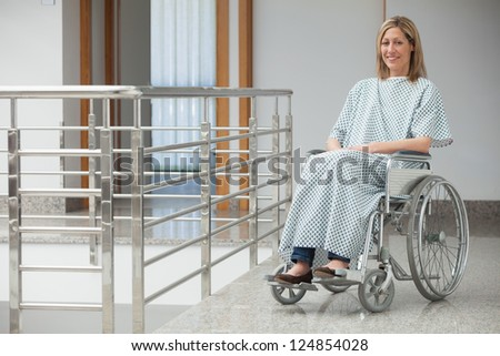 Smiling woman wearing hospital gown sitting in wheelchair in hospital corridor