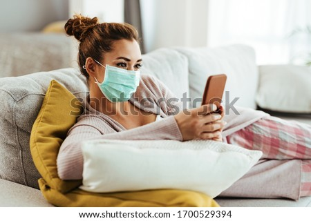 Smiling woman wearing protective face mask while using smart phone and text messaging at home.