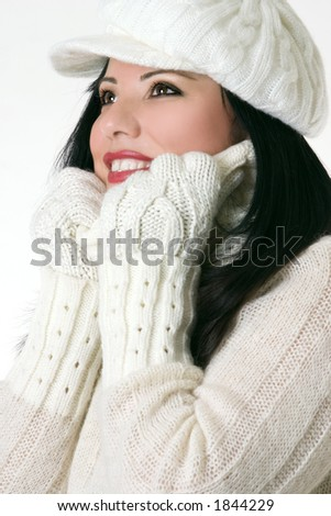 Smiling woman wearing winter hat gloves and polo neck jumper.