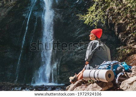 Smiling Woman with backpack dressed in active trekking clothes sitting near the mountain river waterfall and enjoying the splashing Nature power. Traveling, trekking and nature concept image.