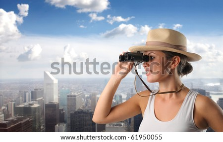 Smiling woman with binoculars and cityscape on the background