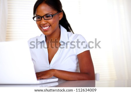 Smiling woman with black glasses working on laptop at office - copyspace