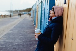 Smiling woman with closed eyes in warm clothes with a reusable cup with a hot drink near colorful beach booths and enjoying the moment. Simple pleasures and personal fulfillment. digital detox.