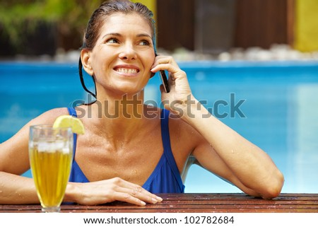 Smiling woman with cocktail and cell phone in swimming pool