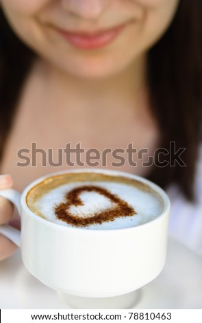 Smiling woman with cup of coffee decorated with heart