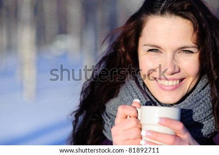 Smiling woman with cup of coffee in the winter park