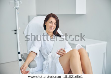 Photo of  Smiling woman with dark hair getting an intravenous vitamin drip treatment at a beauty salon