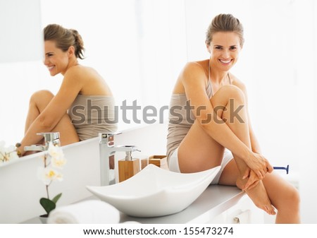 Smiling woman with disposable shaver in bathroom