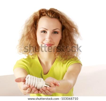 Smiling woman with energy-saving bulb .
