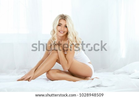 Smiling Woman With Fit Body And Beautiful Legs On White Bed. Happy Girl In White Underwear With Soft Depilated Body Skin, Natural Hair And Beauty Face In Light Interior. Women Skin Care. High Quality