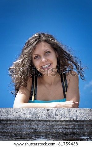 Smiling woman with fly-away hair leans her elbows against column