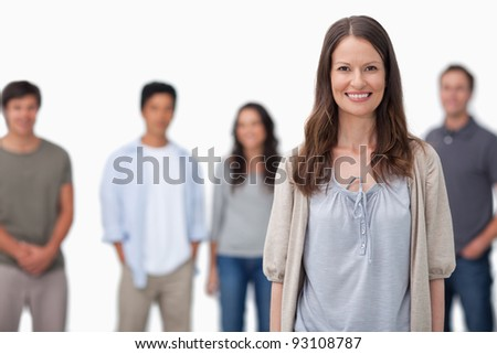 Smiling woman with friends standing behind her against a white background