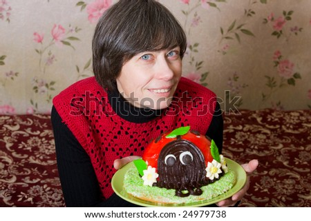 Smiling woman with funny cake on a plate