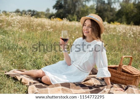 smiling woman with glass of red wine resting on blanket on meadow with wild flowers