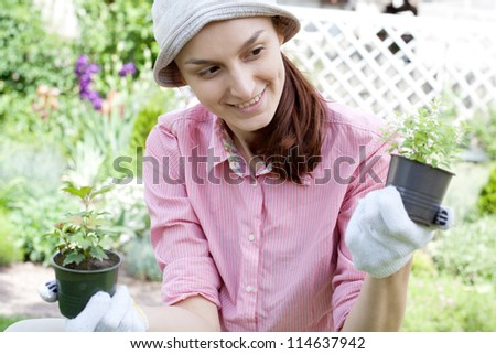 Smiling woman with herbs in garden