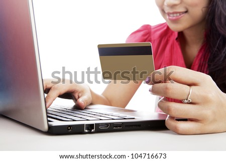 Smiling woman with laptop and a credit card isolated on white
