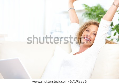 Smiling woman with laptop at home