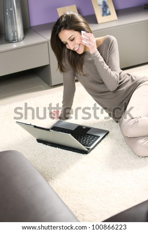Smiling woman with mobile phone and laptop