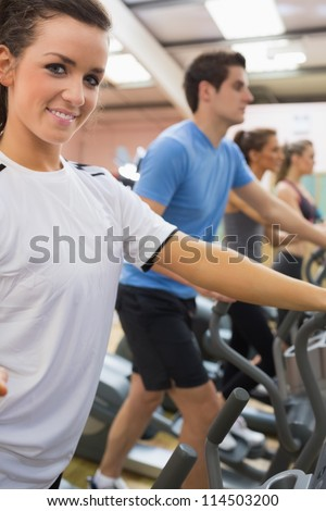 Smiling woman with other people stepping on  step machines in gym